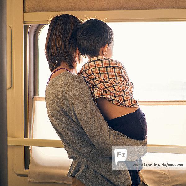 Rückansicht der Frau und des Kleinkindesohnes aus dem sonnendurchfluteten Zugfenster