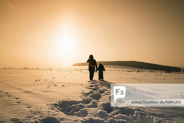 Rückansicht von Mensch und Sohn bei Sonnenuntergang in verschneiter Landschaft  Dorf Sarsy  Gebiet Swerdlowsk  Russland