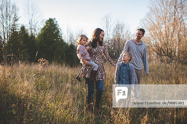 Young couple with son and daughter strolling in field