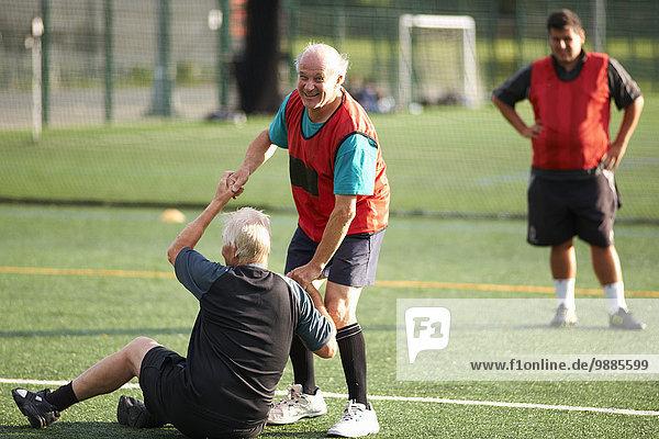 Senior Mann hilft Freund auf dem Fußballplatz aufstehen