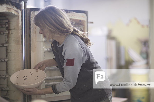 Female potter putting bowl in workshop kiln