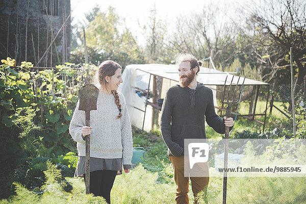 Junges Paar im Garten mit Gabel und Spaten
