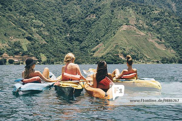 Rückansicht von vier jungen Freundinnen beim Kajakfahren auf dem Lake Atitlan  Guatemala