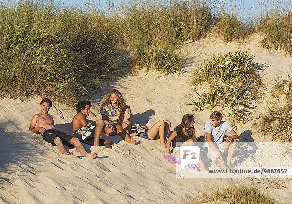 A group of teenagers laying in the sand; Tarifa  Cadiz  Andalusia  Spain