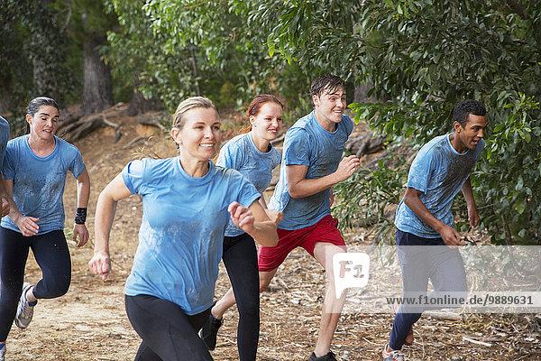 Lächelndes Team läuft auf dem Bootcamp-Hindernisparcours