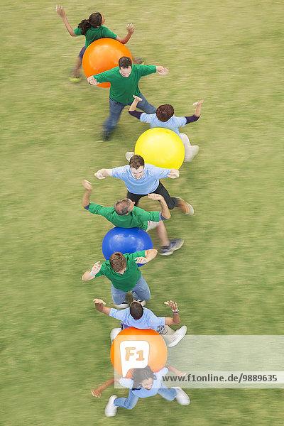 Mannschaftskameraden  die Fitnessball-Teambuilding-Aktivitäten durchführen