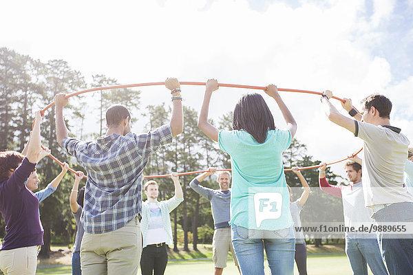 Teambildung verbundener Kreis mit Kunststoffreifen im sonnigen Feld