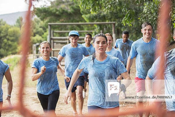 Team läuft im Regen auf dem Bootcamp-Hindernisparcours