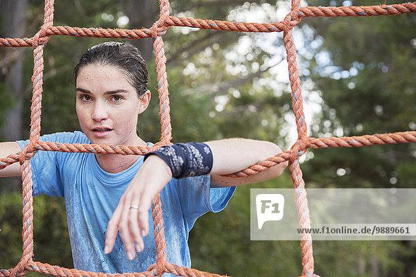 Porträt einer selbstbewussten Frau  die sich im Bootcamp ans Netz lehnt.