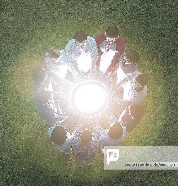 Team im Kreis um die glühende Kugel