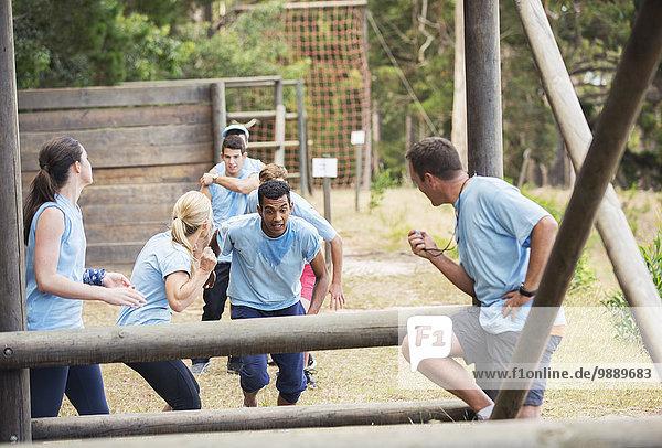 Teamkollegen jubeln Mann auf Boot Camp Hindernisparcours