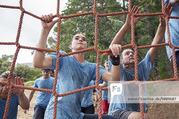 Entschlossenes Frauenkletternetz am Bootcamp-Hindernisparcours