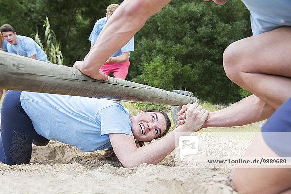 Mannschaftskameradin hilft Frau unter Log auf Bootcamp-Hindernisparcours