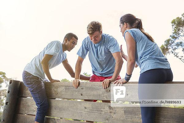 Mannschaftskameraden helfen Mann über Wand auf dem Bootcamp-Hindernisparcours