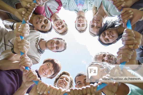 Porträt eines Teams  das im Kreis um den Kunststoffreifen verbunden ist