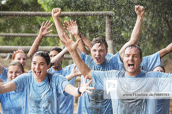 Begeistertes Team jubelt im Regen auf dem Bootcamp-Hindernisparcours