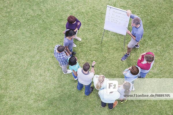 Mann führt Treffen bei Flipchart im Feld an