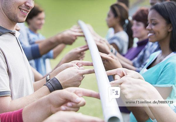 Team Balancierstange mit Fingerspitzen