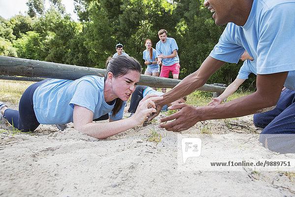 Mannschaftskameradin hilft entschlossener Frau beim Krabbeln auf dem Hindernisparcours im Bootcamp