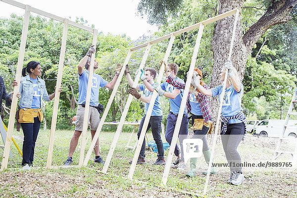 Freiwillige beim Heben von Baukonstruktionen auf der Baustelle