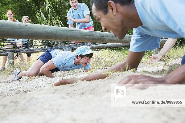 Männer krabbeln unter dem Netz auf dem Boot Camp Hindernisparcours
