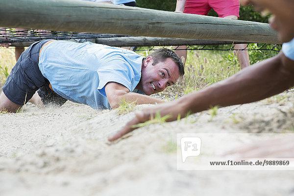 Entschlossener Mann krabbelt unter dem Netz auf dem Bootcamp-Hindernisparcours