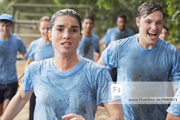 Entschlossene Frau beim Laufen auf dem Hindernisparcours des Bootcamps
