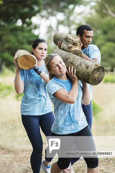 Entschlossene Frau beim Laufen mit Log on Boot Camp Hindernisparcours