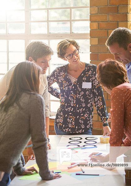 Kreative Geschäftsleute beim Prüfen von Proofs am Tisch