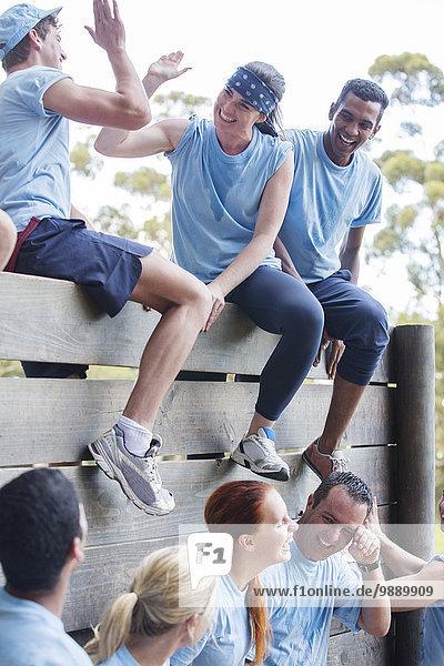 Team feiert an der Wand auf dem Bootcamp-Hindernisparcours