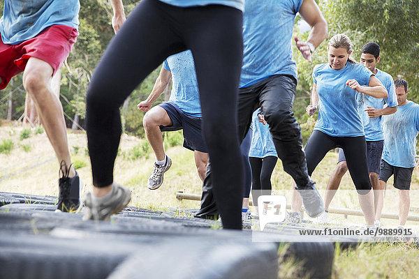 Entschlossene Menschen springen Reifen auf Boot Camp Hindernisbahn
