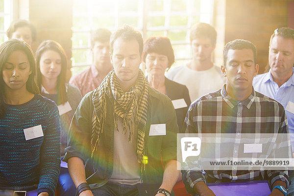 Gelassene Menschen mit geschlossenen Augen im Publikum
