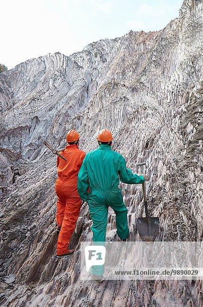 Zwei männliche Arbeiter mit Grabwerkzeugen  außen Salzbergwerk  Rückansicht