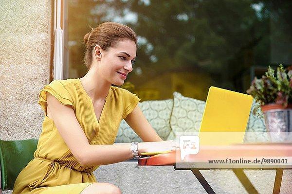Junge Frau mit Laptop außerhalb des Cafés