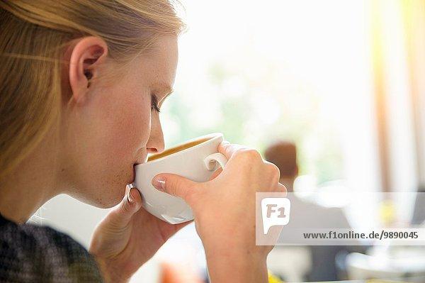 Junge Frau trinkt Kaffee im Café  Nahaufnahme