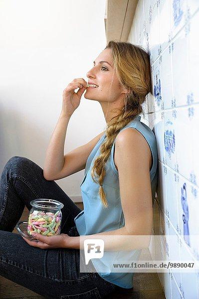 Junge Frau sitzt an der Wand und isst Süßigkeiten aus dem Glas.