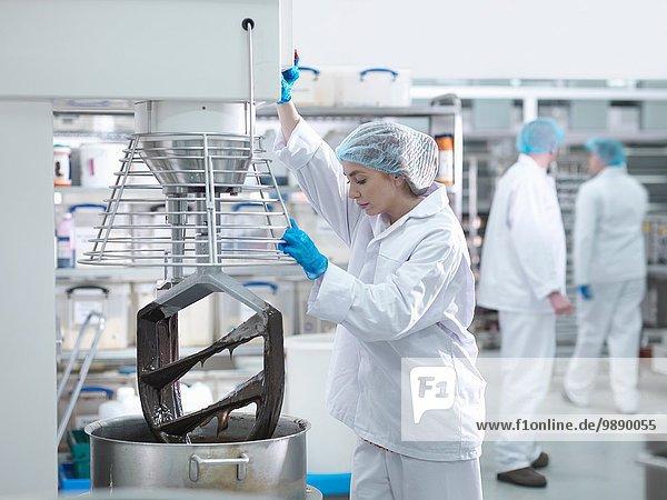 Arbeiterin mischt Schokolade in der Kuchenfabrik