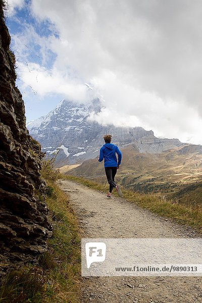 Rear view of man running along dirt track toward mount Eiger  Grindelwald  Switzerland