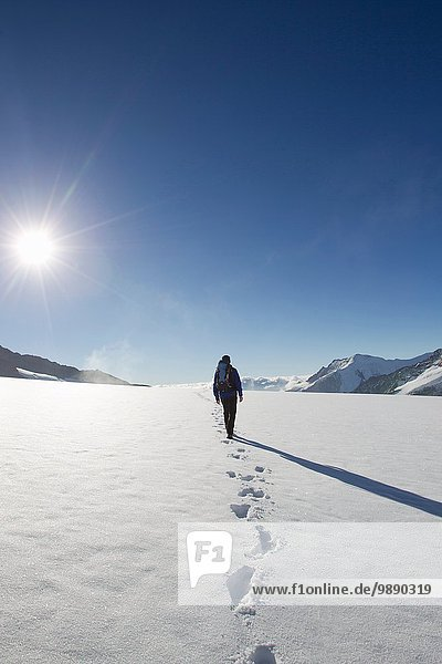 Rear view of male hiker and snow footprints  Jungfrauchjoch  Grindelwald  Switzerland