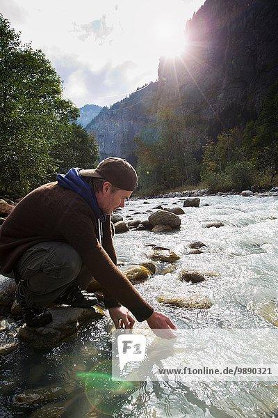 Male hiker crouching down by river  Lauterbrunnen  Grindelwald  Switzerland