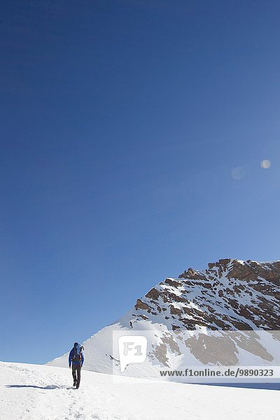 Rear view of man hiking across snow covered landscape  Jungfrauchjoch  Grindelwald  Switzerland