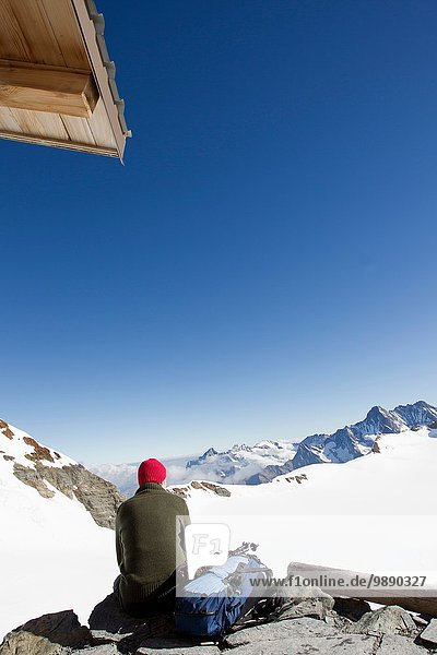 Rear view of male hiker looking out at landscape from viewing platform  Jungfrauchjoch  Grindelwald  Switzerland