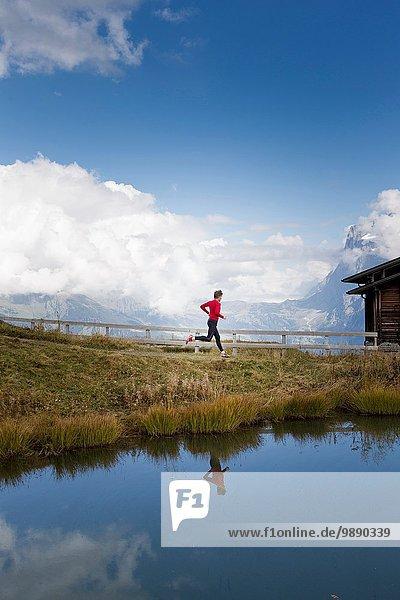Man running along lakeside  Kleine Scheidegg  Grindelwald  Switzerland