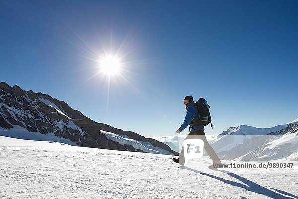 Man hiking across snow covered mountain landscape  Jungfrauchjoch  Grindelwald  Switzerland