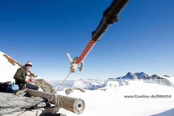 Male hiker eating snacks on viewing platform  Jungfrauchjoch  Grindelwald  Switzerland