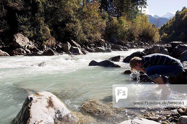 Male hiker washing his face in river  Lauterbrunnen  Grindelwald  Switzerland