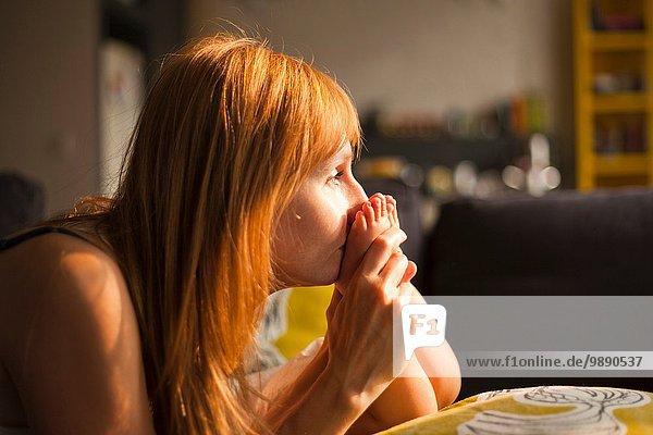Mittlere erwachsene Frau küsst Füße des Kleinkindesohnes im Wohnzimmer