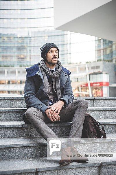 Mid adult businessman sitting on office steps