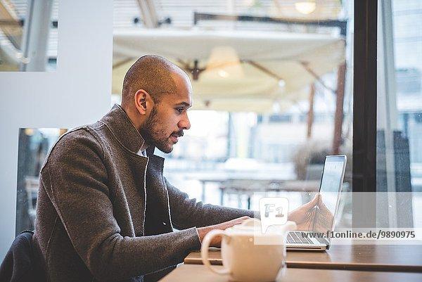 Geschäftsmann sitzt im Cafe und arbeitet am Laptop