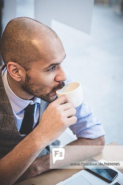 Hochwinkelansicht eines Geschäftsmannes  der im Café sitzt und Kaffee trinkt.